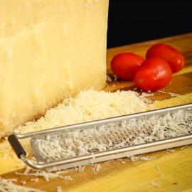 Parmigiano Reggiano Prodotto di Montagna stagionato oltre 24 mesi grattugiato con pomodori di fianco