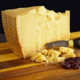 Parmigiano Reggiano stagionato oltre 18 mesi con coltellino a mandorla su tagliere di legno
